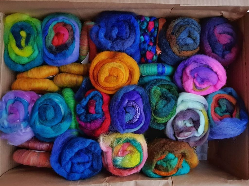 A cardboard box full of rolags and minibatts in saturated colours.