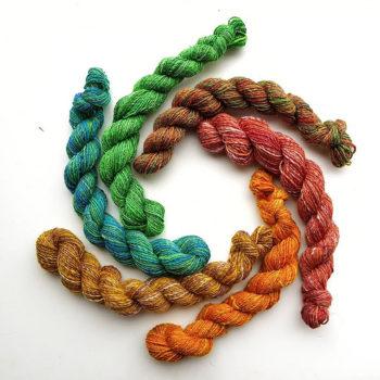 Rainbow skeins. Six mini skeins of yarn, arranged in a circle.