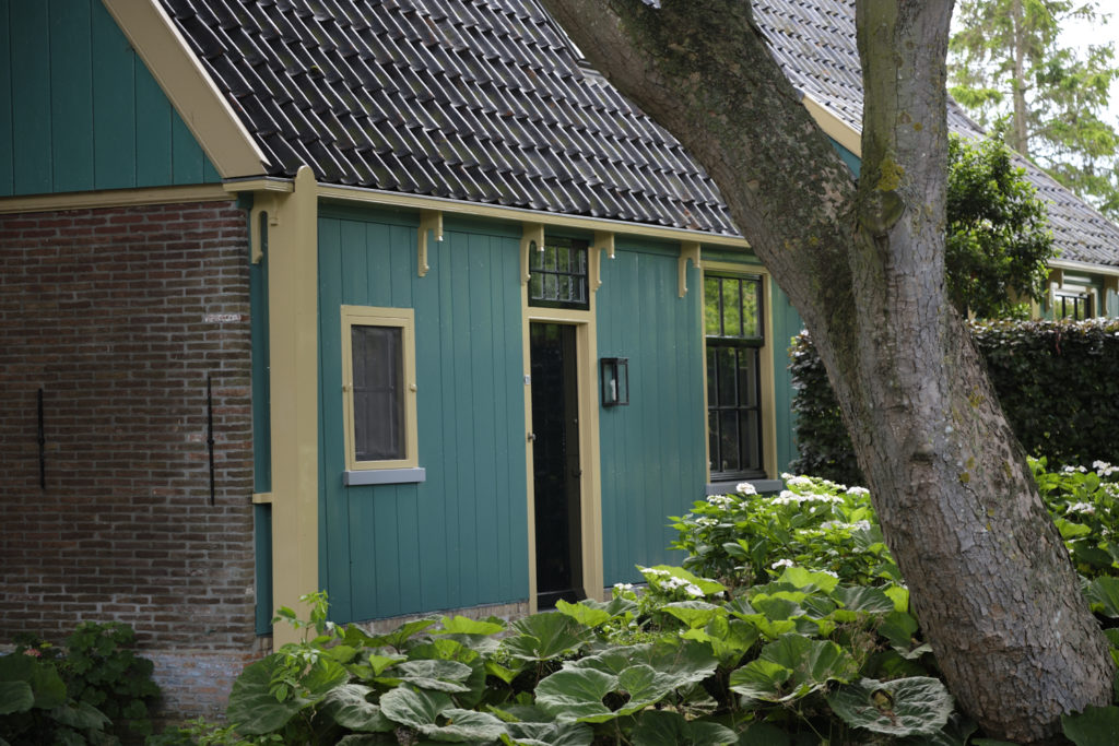 A traditional Dutch house with teal wooden paneling