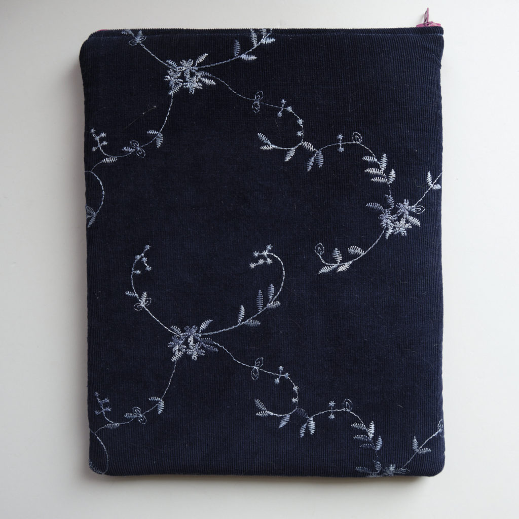 A dark blue iPad sleeve, embroidered with silver leaves. You can just see the pink accent of the zipper.