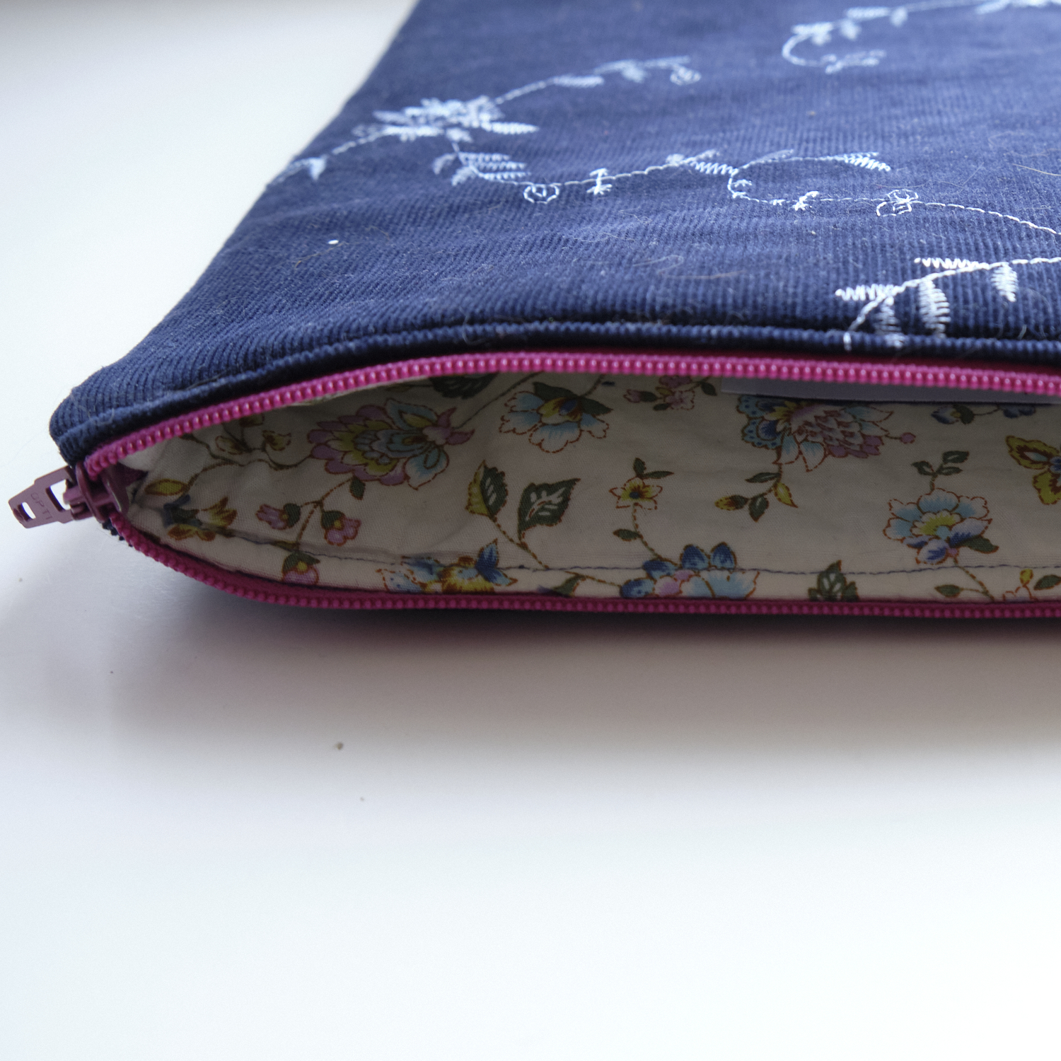 An open, dark blue iPad sleeve with a flowery lining and a pink zipper