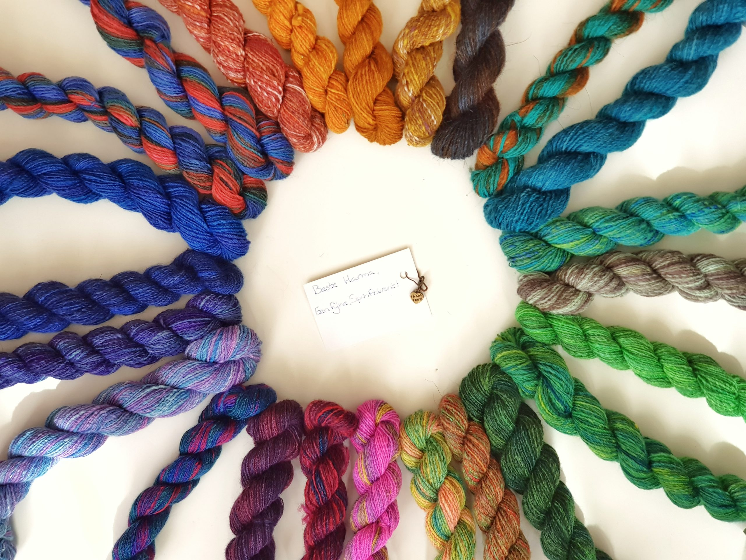 24 mini skeins of yarn in all colours of the rainbow, arranged in a circle
