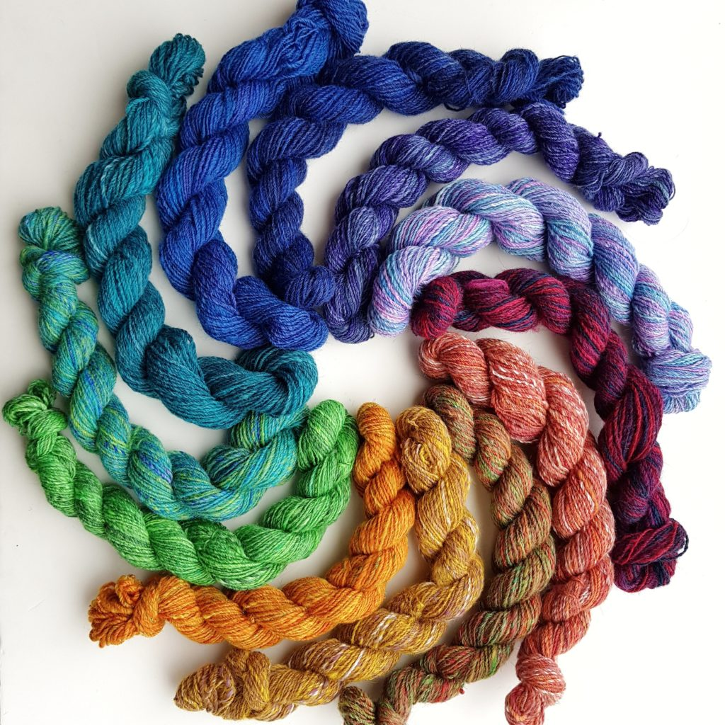 Twelve mini skeins of yarn, arranged in a circle, radiating out. They are ordered by colour, forming a rainbow.
