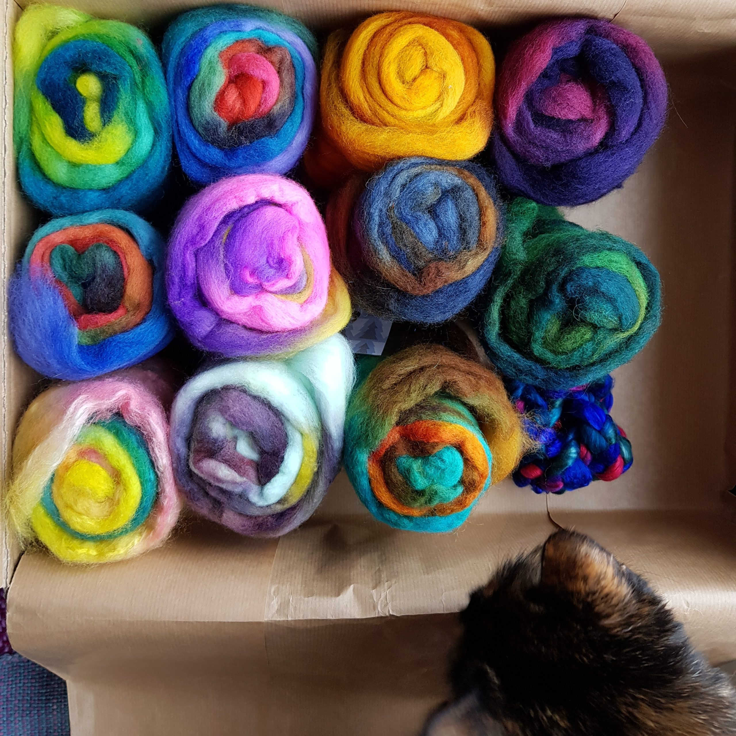 A cardboard box full of minibatts in multiple bright colours.