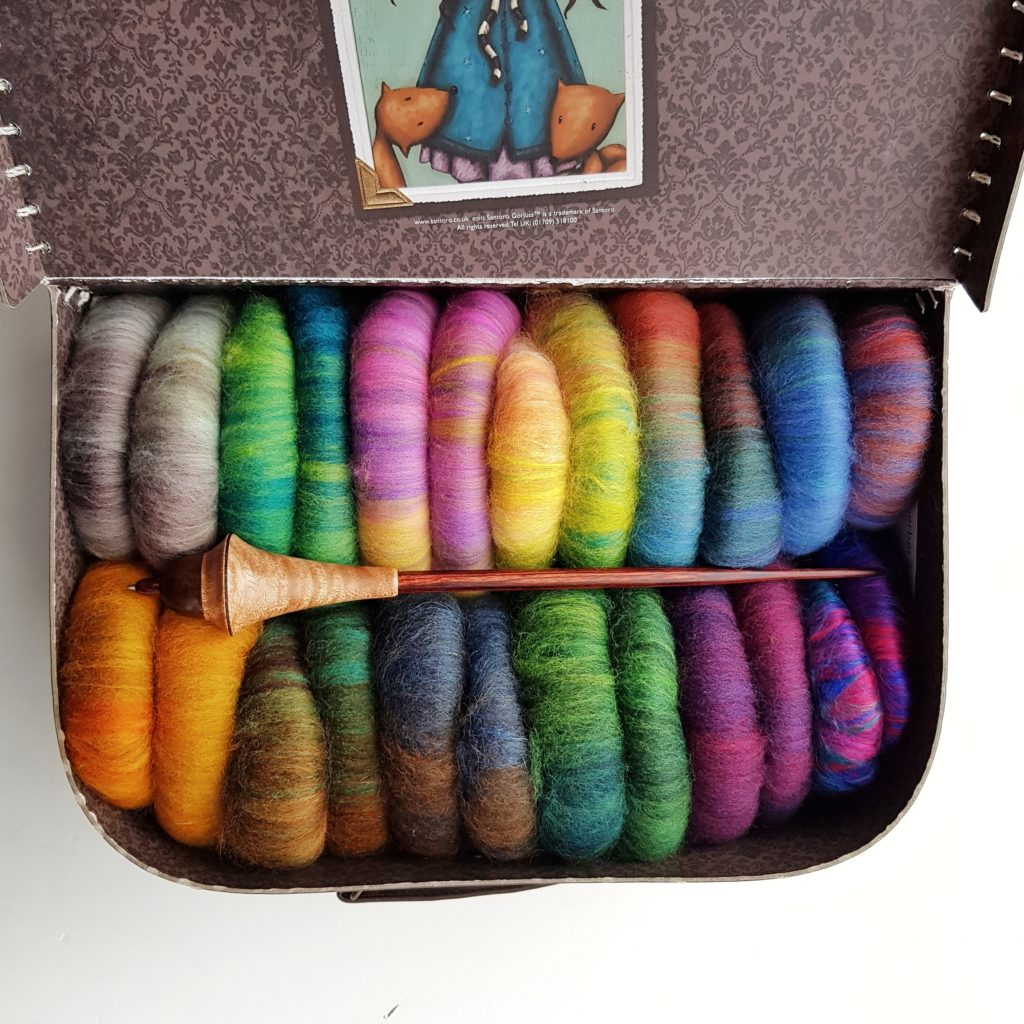 A small suitcase filled with colourful rolags.