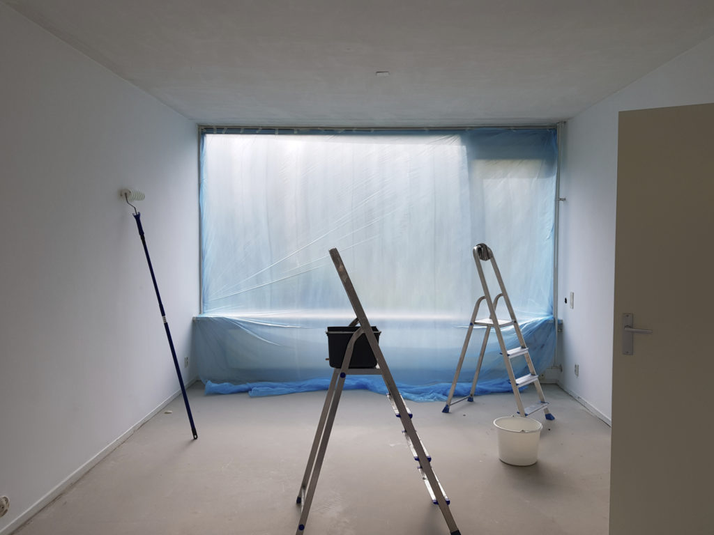 The living room is empty. The window is covered in blue plastic, and painting tools are lying around.
