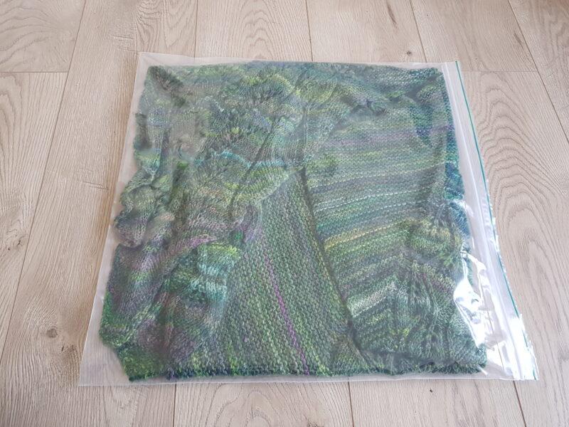 A green hand knit shawl inside a zip loc bag.