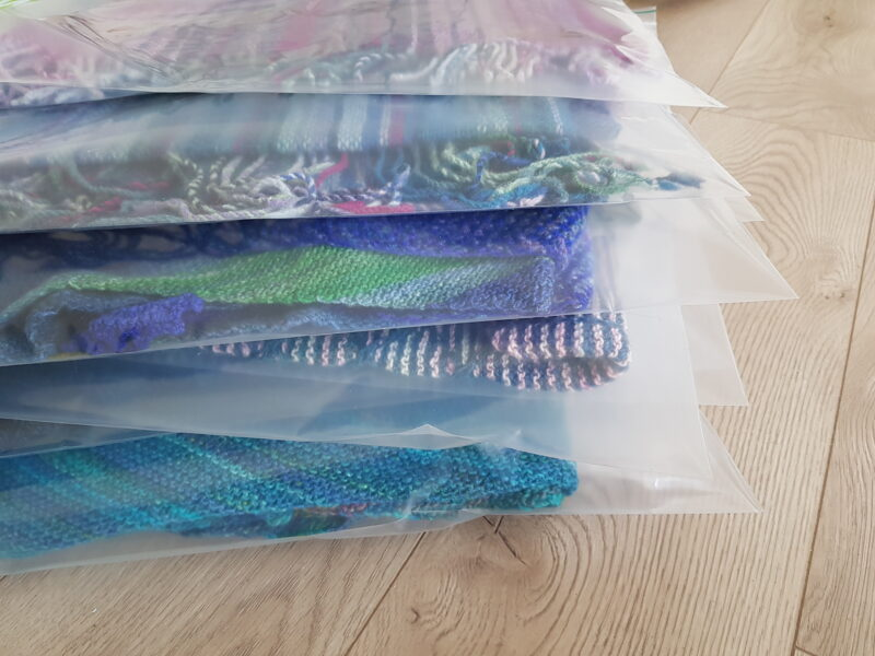 A pile of zip locs containing hand knit items.