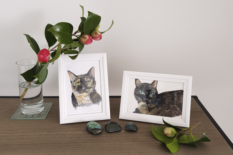 Watercolour portraits of Freya and Fiona. A camellia branch is standing next to the portraits, and there are a few crystals in front.